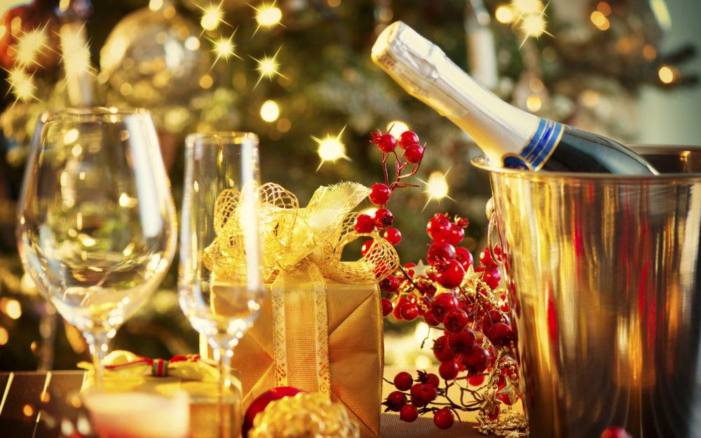 Champagnerkühler mit Champagnerflasch und Gläsern auf einem Tisch in weihnachtlicher Atmosphäre