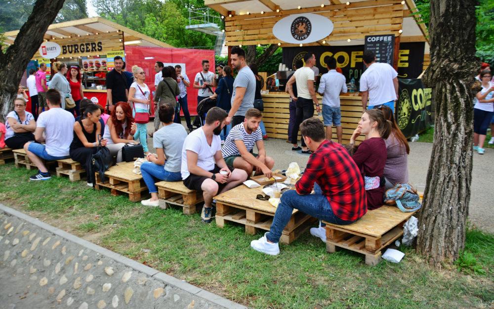 Holzhütten und Holzbänke im Freien mit Besuchern einer Roadshow als mobiles Marketing Instrument