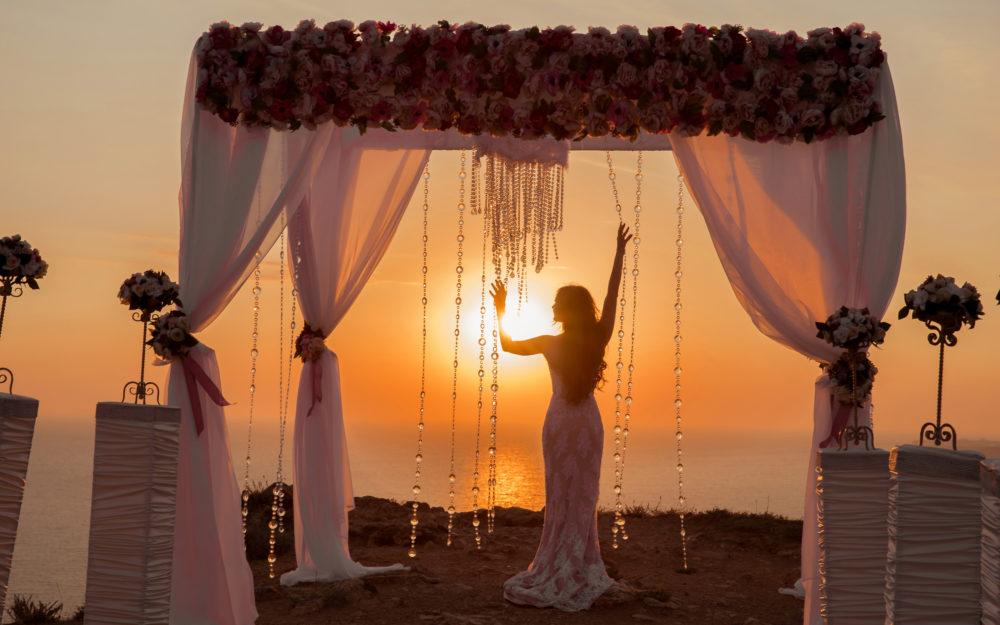 Braut nach ihrer Hochzeit am Meer mit einem Hochzeitszelt und Sonnenuntergang