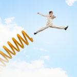 Ein erfolgreicher Sprung in den Himmel mit einer goldenen Sprungfeder als Antrieb