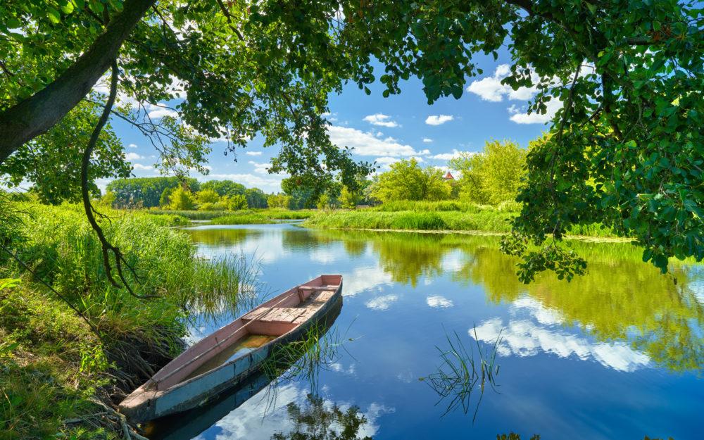 Grüne Natur, ein Fluss mit Boot und blauer Himmel im Sommer