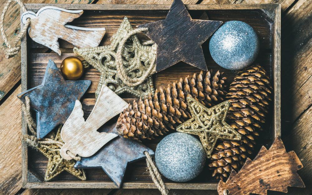 Holzbox mit rustikalen Zapfen, Sternen, Kugeln und Engeln als Weihnachtsdekoration