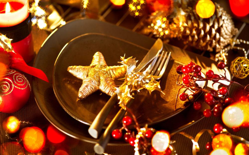 Weihnachtlich dekorierter Tisch mit Tellern, Besteck, Kerzen und Sternen