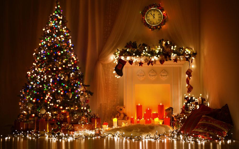 Blick in einen weihnachtlich geschmückten Raum mit Lichtdekoration, Kerzen und einem Weihnachtsbaum