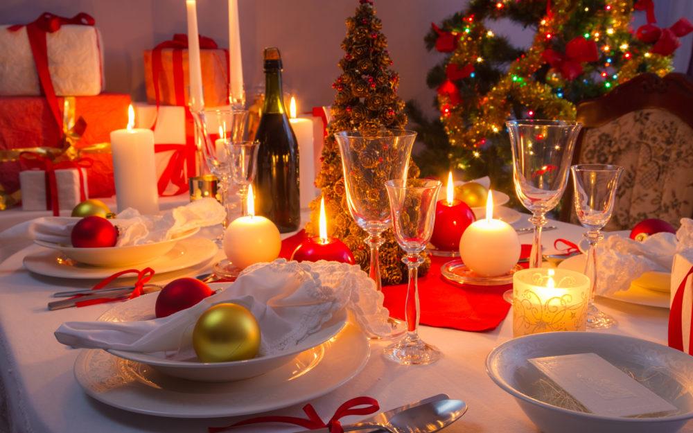 Festlich gedeckter Tisch mit Kerzen und Geschenken in weihnachtlicher Atmosphäre.