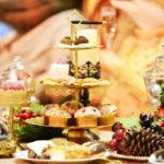 Weihnachtlich dekorierter Tisch mit einer Etagere auf der verschiedenes Gebäck liegt