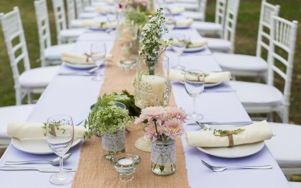 Lange gedeckte Tafel mit Hochzeitsdekoration in weiß