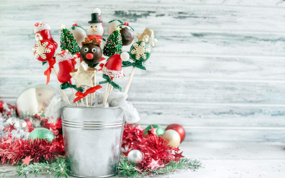 Weihnachtliche Cake Pops in Form von Schneemännern, Tannenbäumen und Stiefeln stehen in einem kleinen Eimer