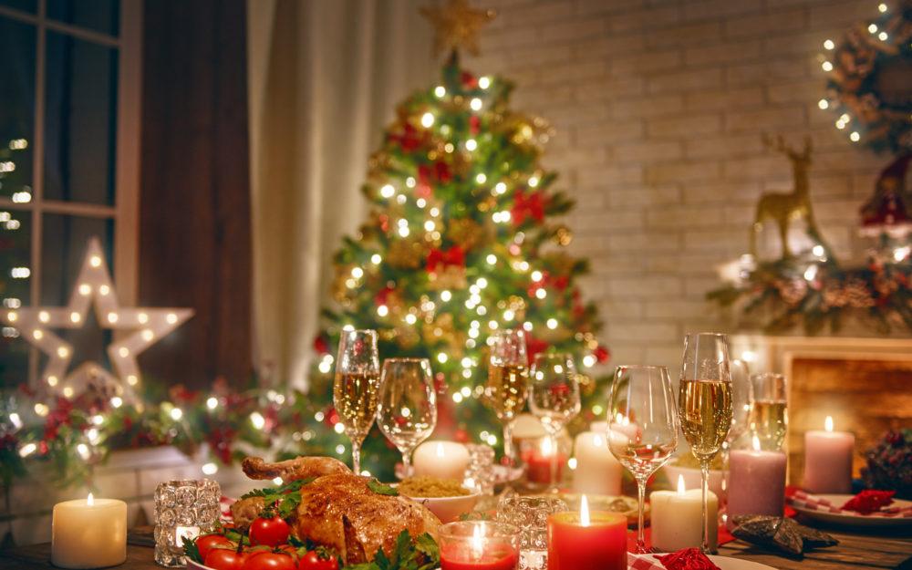 Gedeckter, weihnachtlich geschmückter Tisch mit einem Braten und Sekt und im Hintergrund einen Weihnachtsbaum