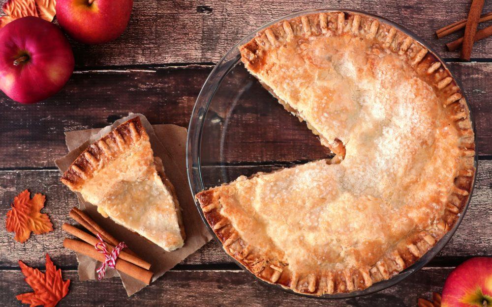 Ein gedeckter Apfelkuchen auf einem Holztisch
