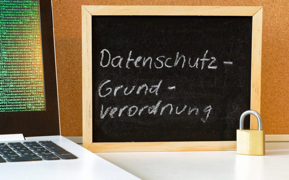 Tafel mit der Aufschrift DSGVO (Datenschutzgrundverordnung) in englisch GDPR (General Data Protection Regulation) mit einem Laptop und Vorhängeschloss zur Einführung der DSGVO in der EU am 25.05.2018