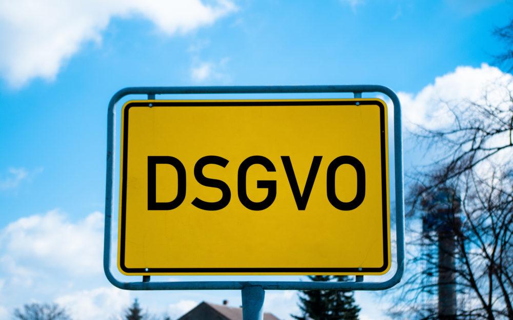 Ortsschild mit Aufschrift DSGVO mit gelbem Hintergrund und hellblauem Himmel mit Wolken