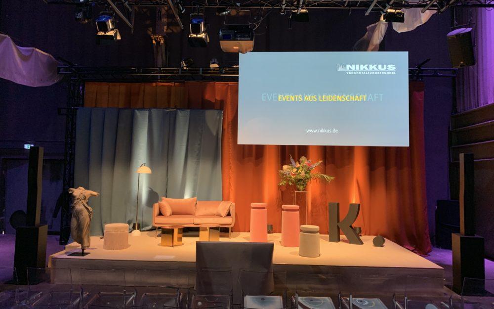 Bühne mit Couch und rotem Vorhang, gemütlich beleuchtet