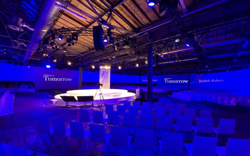 Blau beleuchtetes Business Event mit hell angestrahlter Bühne