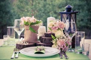 Rustikale Tischdekoration für eine Hochzeit mit Blumen, Holzscheiben und einer Laterne