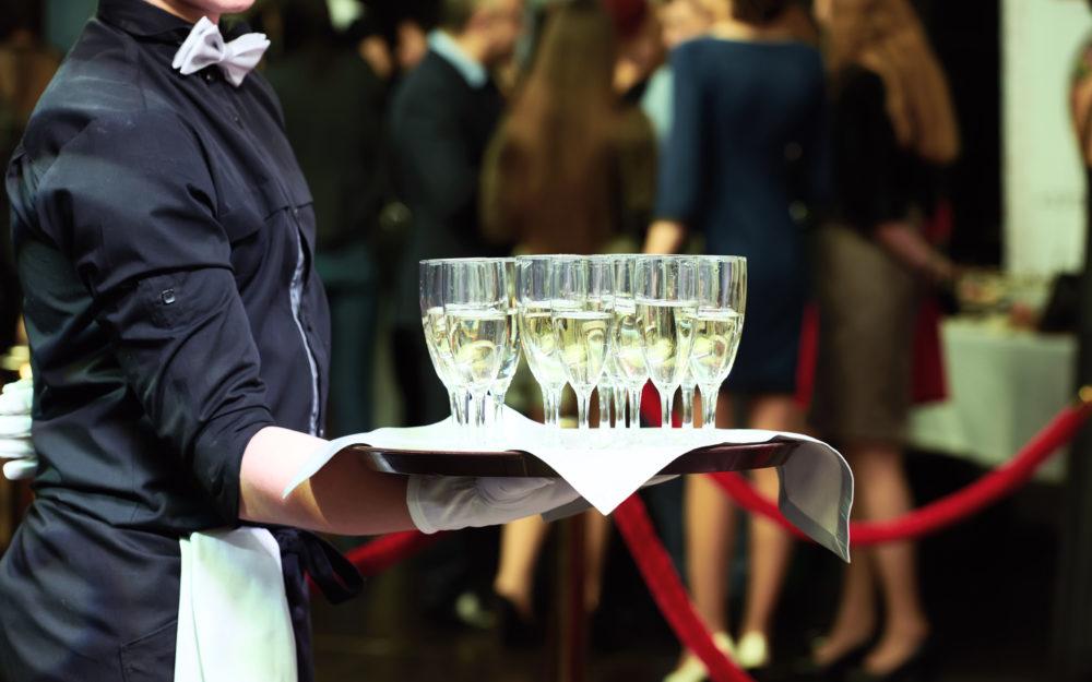 Ein Kellner mit einem Tablett mit vollen Sektgläsern auf einer Veranstaltung