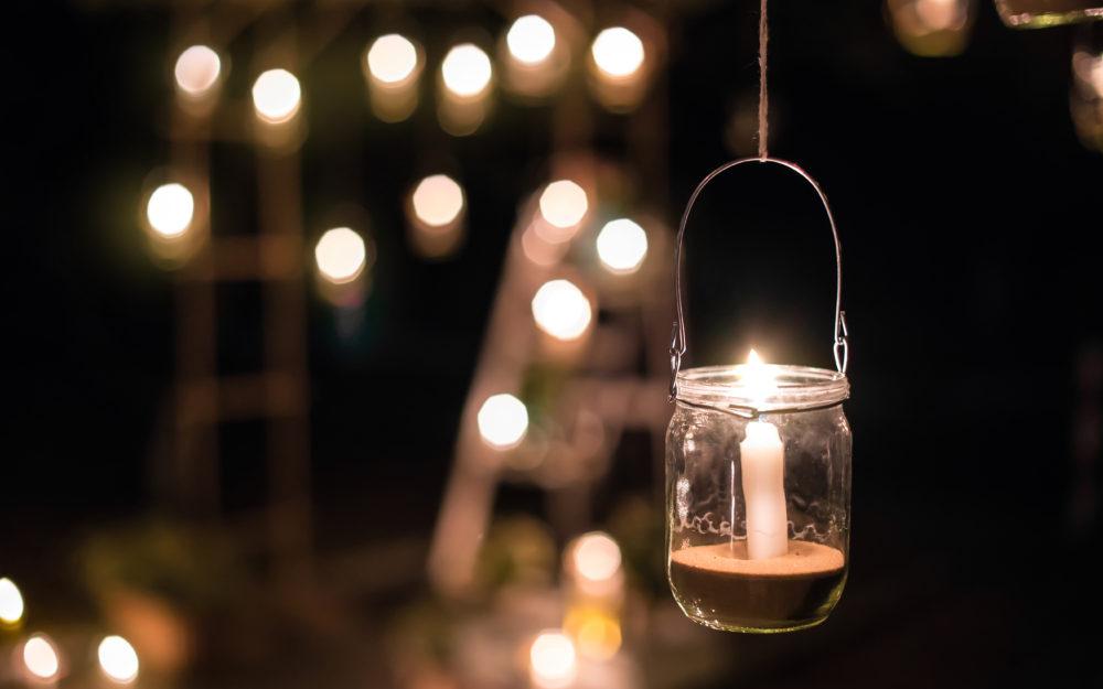 Hängendes Glas gefüllt mit Sand und einer Kerze