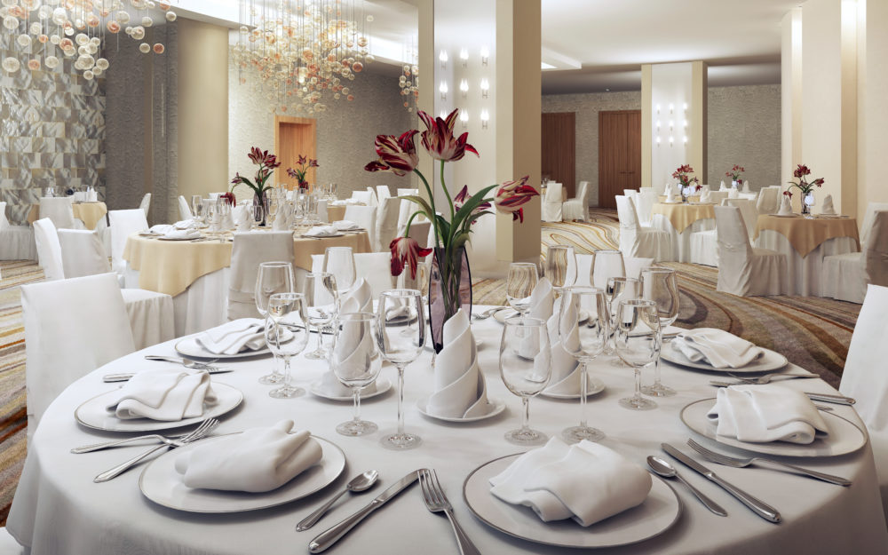 Elegant dekorierter Veranstaltungsraum mit runden weißen Tischen und roten Blumen