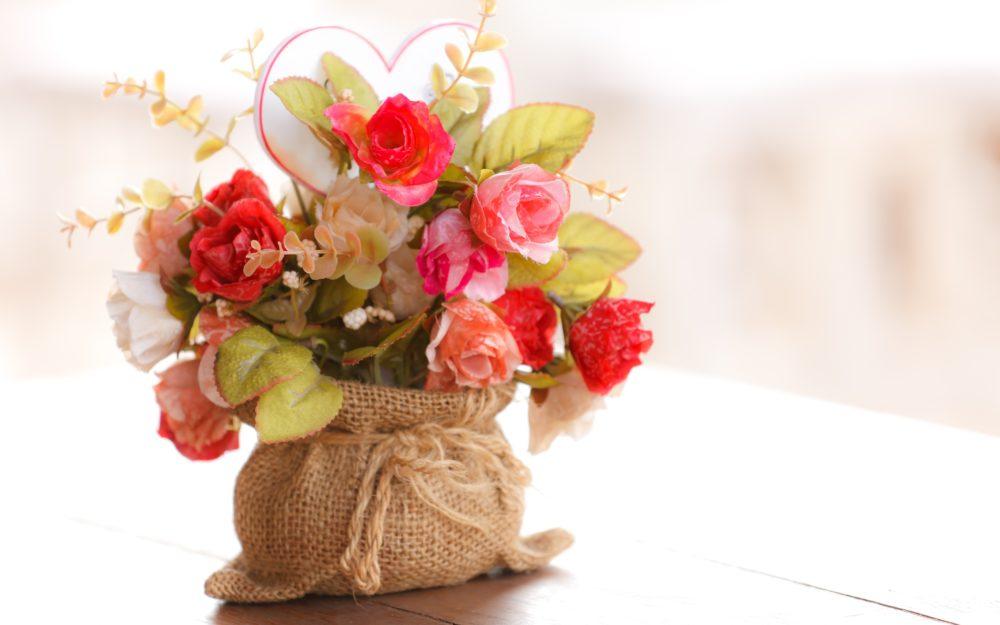 Topf mit Blumen in einem dekorativen Leinensack