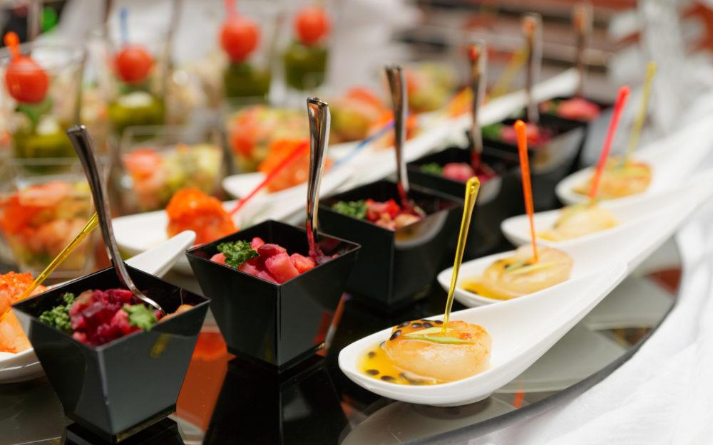 Häppchen und Snacks in kleinen Gläschen und Schalen auf einem Buffet