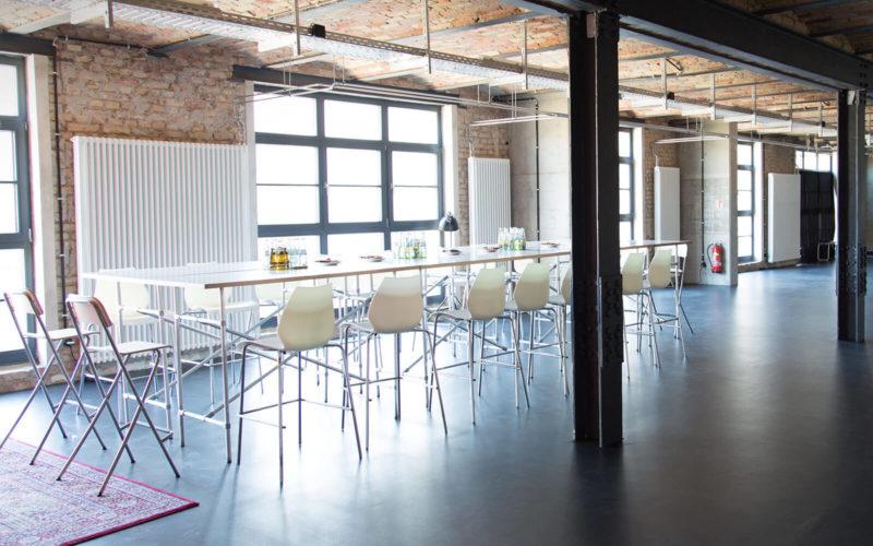 Industriehalle mit langem Tisch und weißen Barstühlen