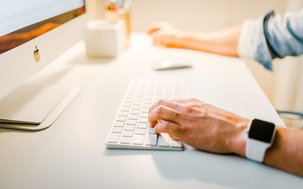Weißer Schreibtisch mit weißem PC und Tastatur