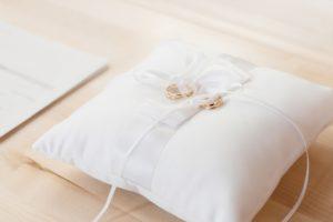 Weißes Hochzeitskissen mit goldenen Ringen