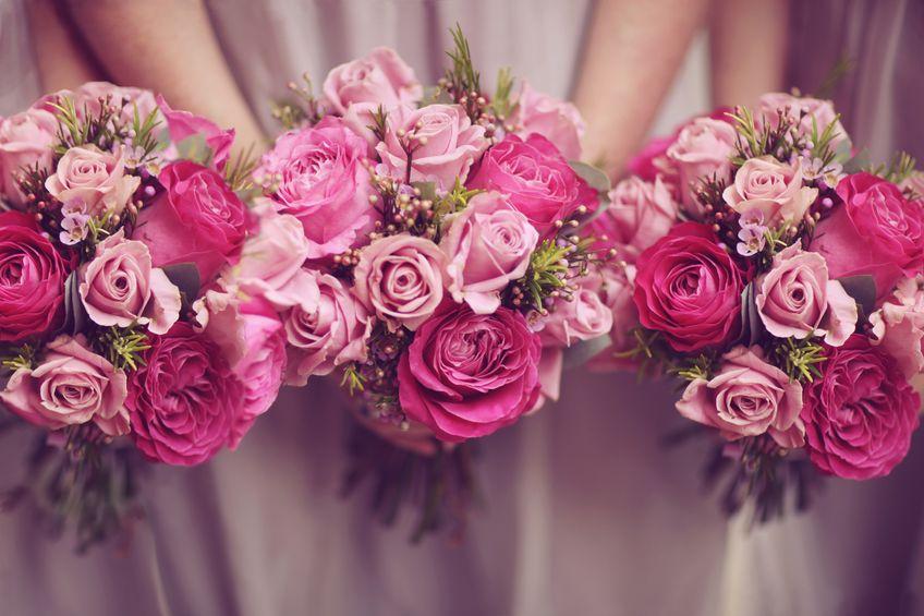 Drei Brautjungfern in rosanem Kleid halten drei pinke Blumensträuße