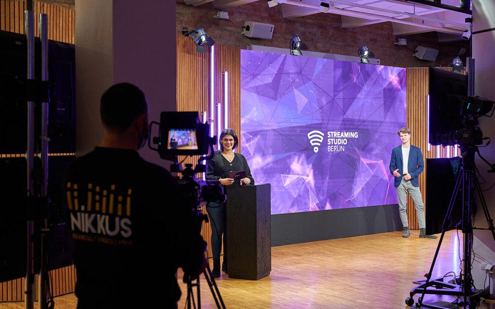 Große Leinwand mit zwei Moderatoren und einem Kameramann