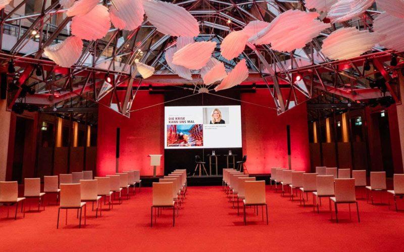Reihenbestuhlung im Tagungsraum mit rotem Teppich und Leinwand