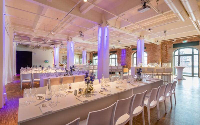 Eventlocation ganz in weiß gehalten mit gedeckten Tischen und Blumenbouquets