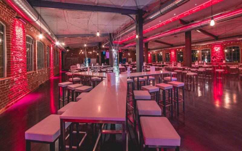 Weißer Tresen mit Hockern und rotes Licht im Loft