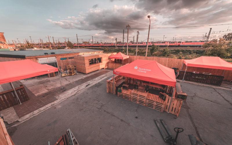 Outdoor Verkaufsplatz von oben mit rotem zug Bierbänke Sonnenschirme