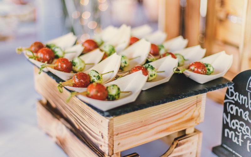 Tomaten-Mozzarella Spieße in Bambusschiffchen auf Schieferplatte und Kiste