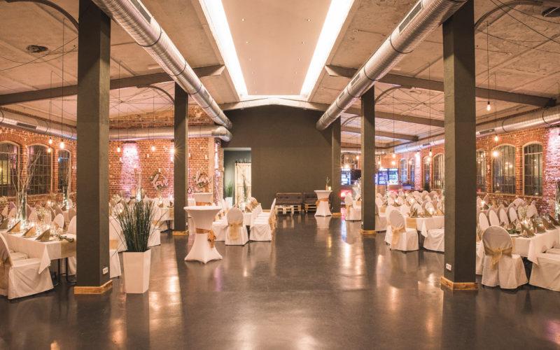 Eventlocation mit gedeckten Tischen mit weißer Tischdecke und Stuhlhussen