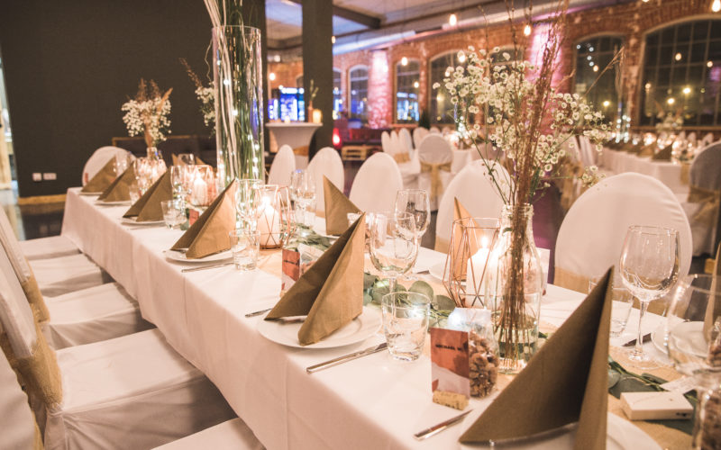Festlich gedeckter Tisch für mehrere Gänge in weiß mit Blumen