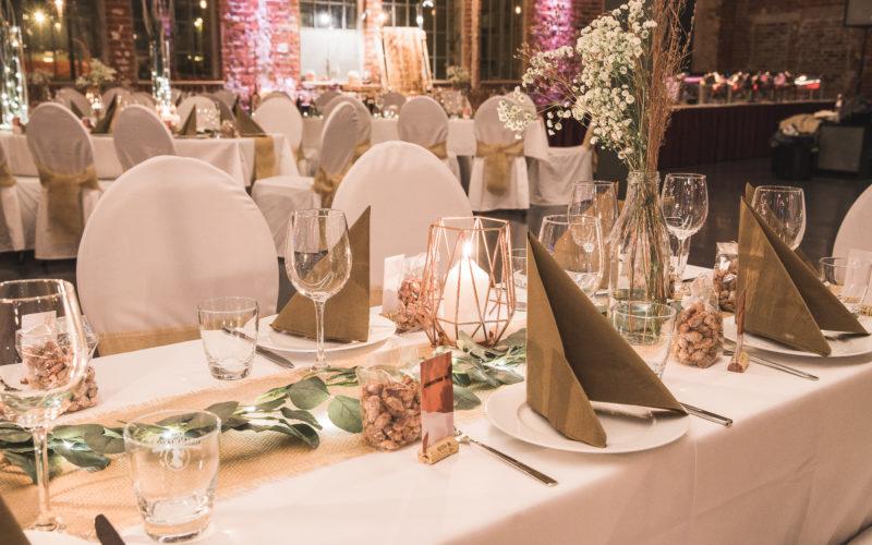 Gedeckter Tisch mit weißer Tischdecke und Stuhlhussen