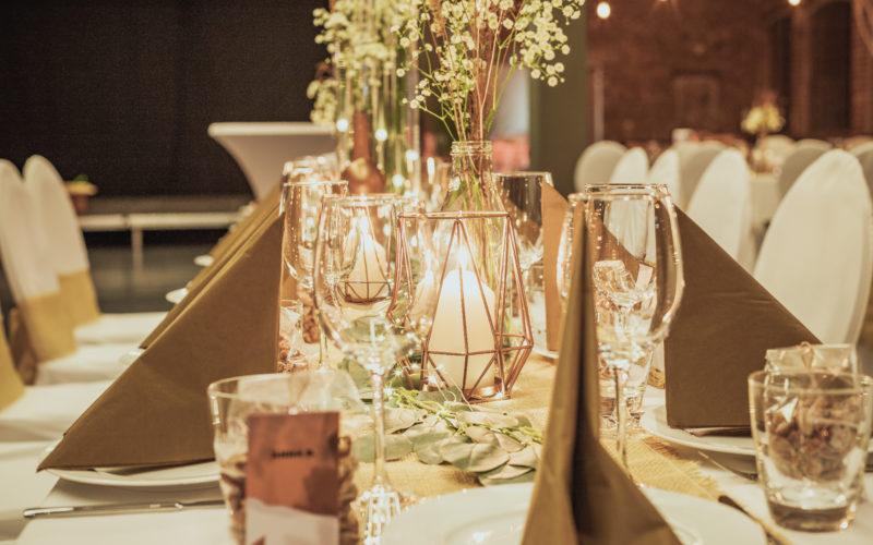 Gedeckter Tisch mit Blumendeko in Flasche Kerzen und Gläser braune Servietten
