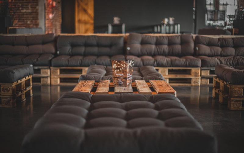Sitzgelegenheit mit braunem Kissen auf Paletten