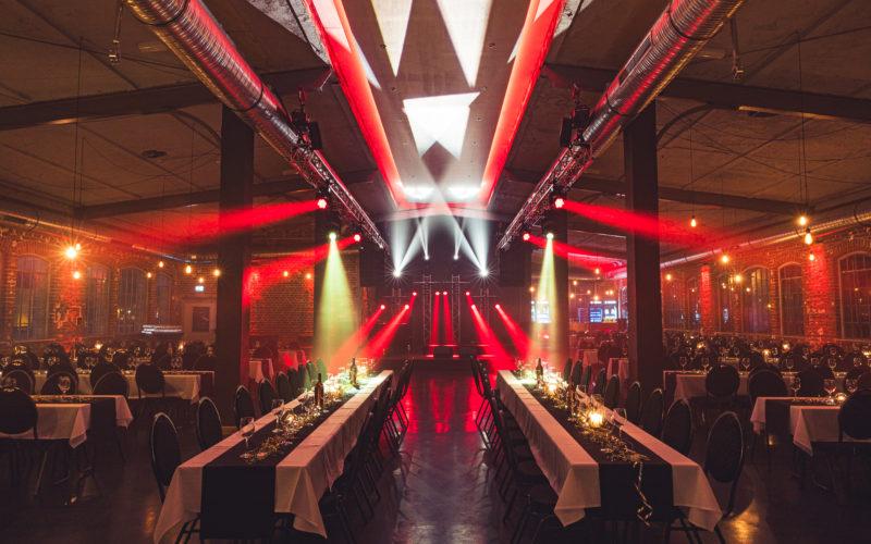 Eventraum mit gedeckten Tischen mit Gläser und Kerzen mit roter Lichtschow