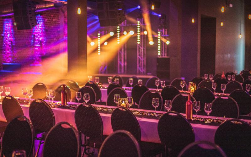 Eventlocation mit Lichtshow mit Stuhlreihen und Tischen